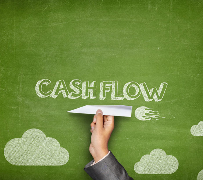 Cash flow concept on green blackboard with businessman hand holding paper plane